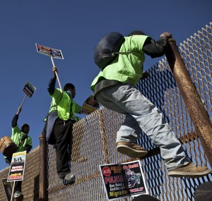 Deported migrants climb a fence at the U.S.- Mexico border as they prepare for the 6th annual Marcha Migrante, or Migrant March in Tijuana, Mexico, Wednesday Feb. 2, 2011. The Tijuana to Mexicali pilgrimage is organized by the group Border Angels to raise awareness on immigration issues. Marchers are demanding a stop of nighttime deportations and human rights abuses by police on both sides of the border. (AP Photo/Guillermo Arias)